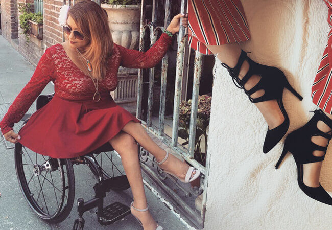A women sitting on a wheelchair in a beautiful red dress and black high heels