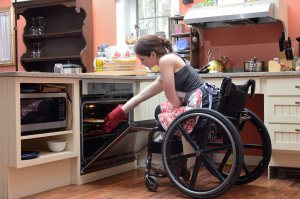 kitchen 300x199 - Young woman using a wheelchair cooking in her adapted kitchen