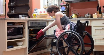 Woman in wheelchair taking tray out of oven