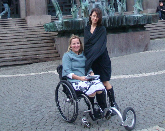 deborah sitting on a wheelchair in sweden with her daughter standing beside her