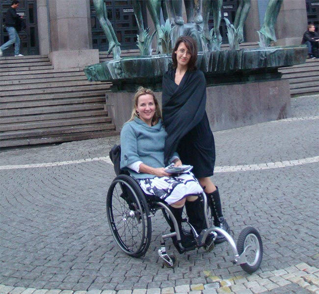 deborah sitting on a wheelchair in sweden with her daughter standing beside her