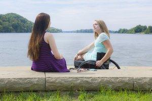 PL 1SBSON0 original 1 300x200 - A blonde girl sitting in a wheelchair talking to a friend