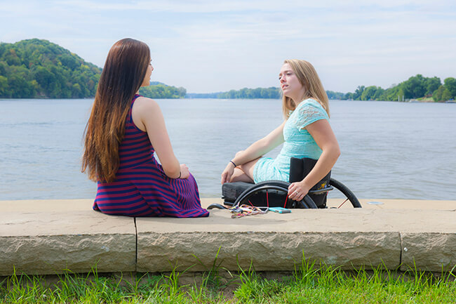 A blonde girl sitting in a wheelchair talking to a friend