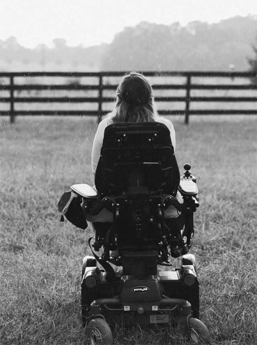 Black and white image of a woman in electric chair facing a horizon and wooden fence in field seen from behind.