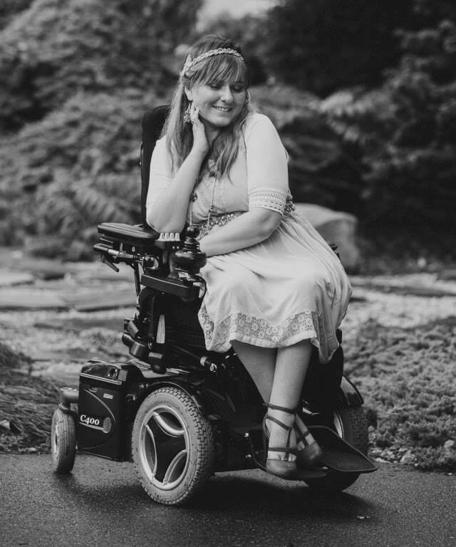 Black & white photo of a beautiful disabled girl sitting in her power wheelchair and smiling