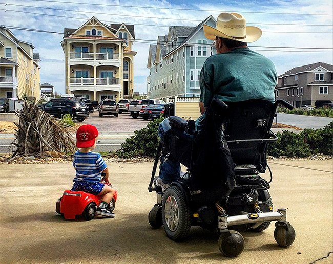 a disabled man sitting on a wheelchair looking at a real estate property along with a little boy sitting beside on his bike