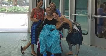 three women sitting at swim area standing and smiling with a disabled women sitting on a wheelchair