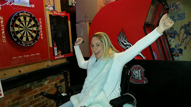 Disabled women sitting in arcade playroom on a wheelchair smiling and cheering