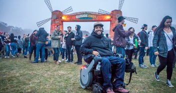 man shown at an outdoor festival smiling in an electric WHILL wheelchair