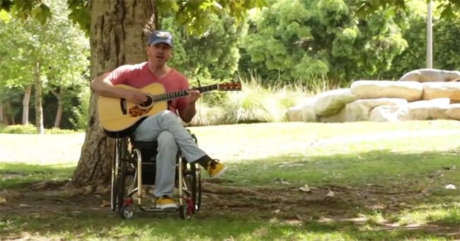 Disabled men sitting on a wheelchair in a garden playing guitar