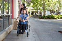A women pushing a disabled women wearing a blue shirt on a wheelchair