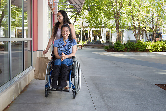 A women pushing a disabled women wearing a blue shirt on a wheelchair