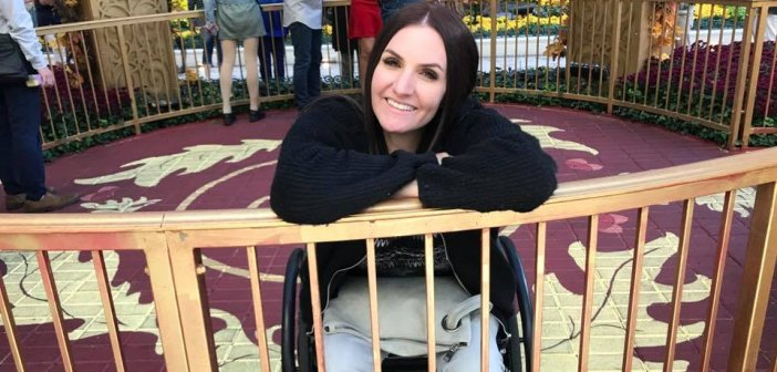 Gina shown sitting in wheelchair smiling while behind a gated circle made of gold in a out door mall