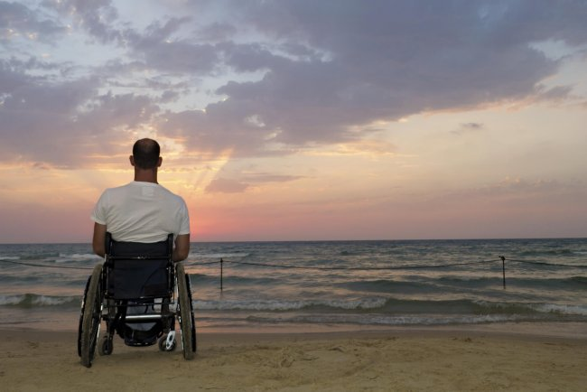 man sitting in a wheelchair patiently waiting for a sunrise