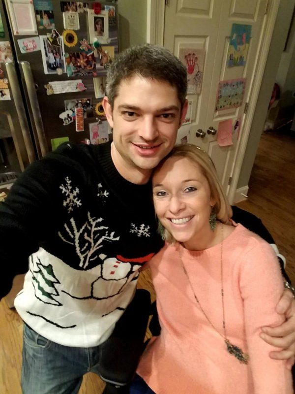 Ali-pictured-with-her-boyfriend-Aaron-standing-with-his-arm around-her-while-sitting-inn-her-wheelchair