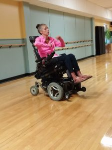 PL 1S3VLCS original 225x300 - Young woman using a power wheelchair exercising in a dance studio