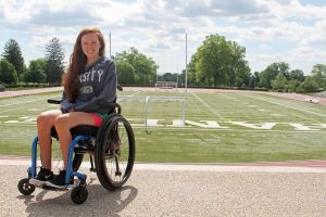 PL DZBFTHQ original 300x200 - Young woman in a wheelchair at a campus sports ground