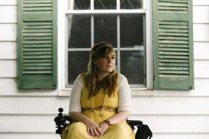 PL 1QFJJBH original 1 300x200 - Young woman in a power wheelchair enjoying her home garden