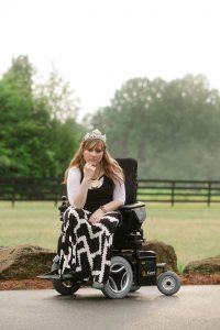 PL QTIBTWV original 2 200x300 - Young woman in a power wheelchair enjoying her home garden
