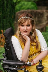 PL TJGB3AO original 2 200x300 - Young woman in a power wheelchair enjoying her home garden