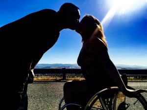 PL 6BT6IHG original 1 300x225 - Young woman in a wheelchair kissing her boyfriend silhouetted against the sun