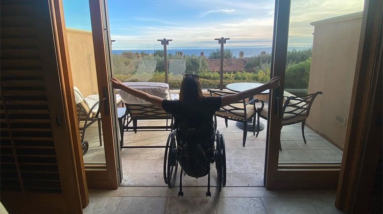woman in wheelchair looking at window
